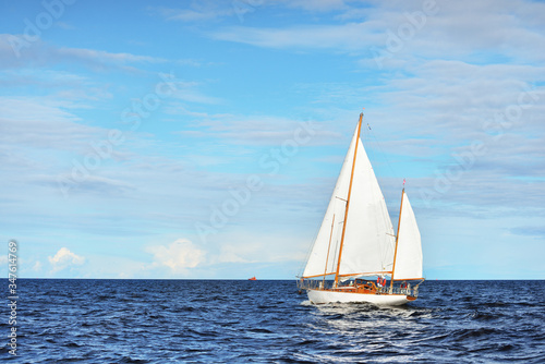 Fototapeta Old expensive vintage wooden sailboat (yawl) close-up, sailing in an open sea