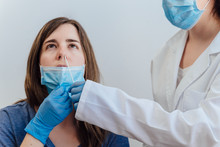 Female Doctor In A Protective Suit Taking A Nasal Swab From A Person To Test For Possible Coronavirus Infection. Nasal Mucus Testing For Viral Infections. Medical Concept. Covid