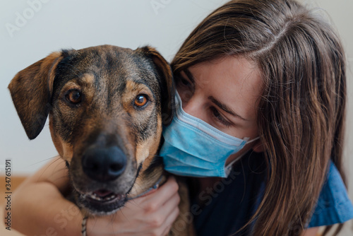 Fototapeta woman with dog wearing hand made protective face mask, in nursing care home, looking outside window with sadness in her eyes, self isolation due to the global COVID-19 Coronavirus pandemic