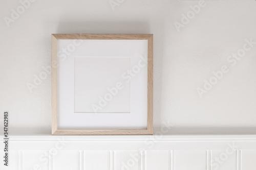 Closeup of square empty wooden picture frame on shelf Slika na platnu