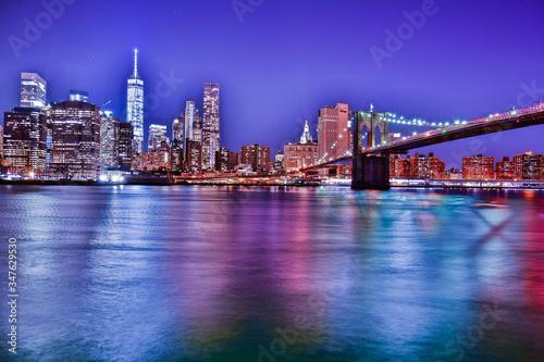 Fotografering Illuminated Brooklyn Bridge Over East River Against Sky At Dusk
