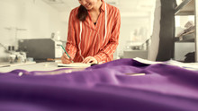 Believe In Your Creativity. Cropped Shot Of Young Female Clothing Designer Leaning Against The Desk With Fabric, Textile And Sewing Supplies On It, While Planning New Collection And Writing Notes