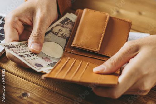 Valokuvatapetti 財布からお金を出す人