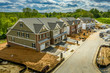 canvas print picture - Elevated view of almost finished luxury townhouses with two single car garages, brick and shake and shingle siding, gable roof with attic vent on a new residential development in Maryland USA