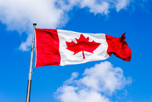 Waving Canadian Flag With Blue Sky In Background