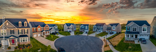 Obraz Cul de sac classic dead end street surrounded by luxury two story single family homes in new residential East Coast USA real estate suburban neighborhood dramatic colorful yellow orange sunset sky - fototapety do salonu