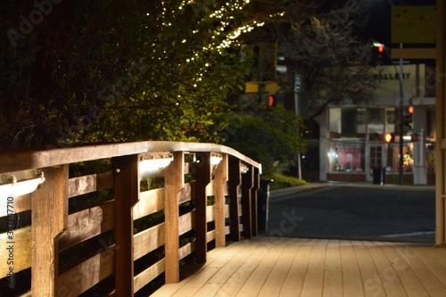 Fotografia Wooden Footbridge Leading Towards Street At Night