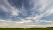 Plumose clouds in the blue sky, nature background, time lapse. Spring field landscape.