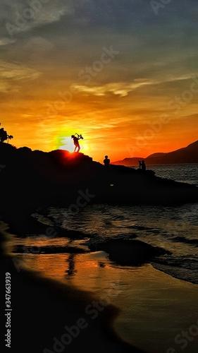 Vászonkép Silhouette People On Rocks Against Orange Sky