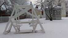 Snow Covered Swing On Field During Winter