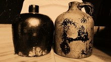 Close-up Of Old Jugs On Table