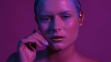 Elegant Model With Painted Face Stands Under Neon Purple And Looks Into Camera. Her Hands Move Very Softly. Video Is Taken In Slow Motion