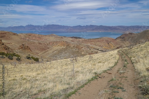 A backcountry dirt road descends toward a scenic distant lake. Canvas Print