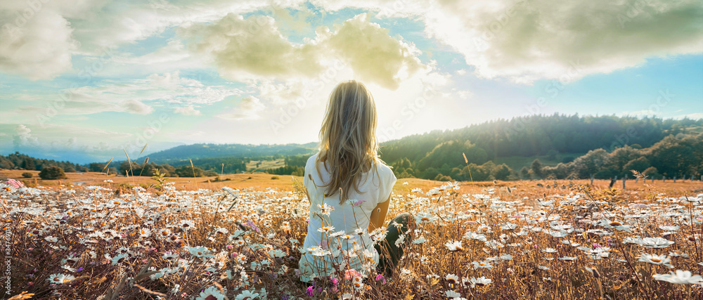 Fototapeta Woman sitting on the chamomiles field and looking at the cloudy sky at sunset. Banner edition..