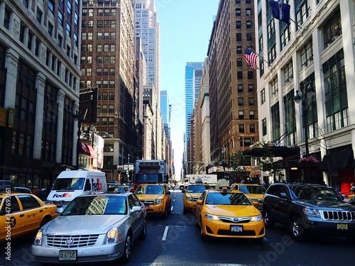 Fototapeta Vehicles On City Street Amidst Buildings obraz na płótnie