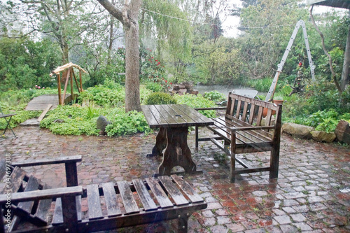 Photo Empty Wet Wooden Furniture In Yard During Rainy Season