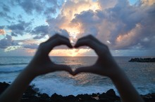 Cropped Hand Making Heart Shape Against Sea During Sunset