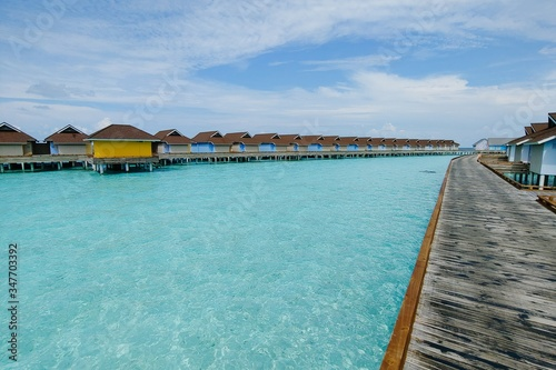 Foto Beautiful shot of a luxury water villa resort with a wooden pier in the Maldives