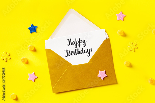 Fotografija Happy Birthday card in a golden envelope, shot from above on a yellow background