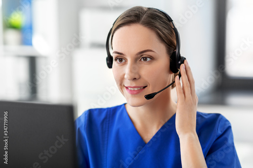 Fototapeta medicine, technology and healthcare concept - happy smiling female doctor or nurse with headset and computer working at hospital obraz