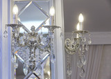 Two wall chandeliers in the form of candles on the mirror surface.