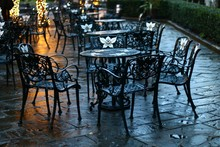 Empty Chairs And Tables On Wet Footpath At Sidewalk Cafe