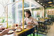 canvas print picture - Asian woman sitting separated in restaurant eating food with table shield plastic partition to protect infection from coronavirus covid-19, restaurant and social distancing concept