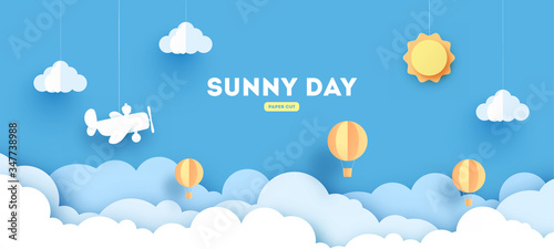 Obraz Cloudscape , blue sky with clouds and sun , paper art style. concept. paper cut design with balloons and airplane. - fototapety do salonu