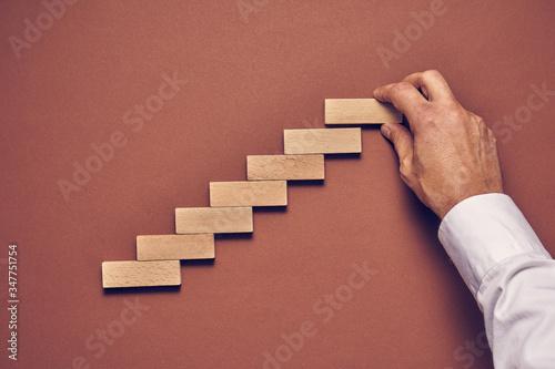 Obraz Męska dłoń i drewniane klocki ułożone w konceptualnym wizerunku - fototapety do salonu