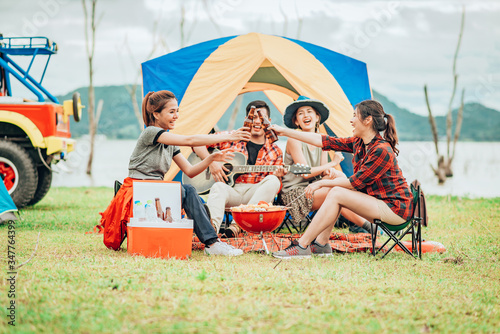 Obraz Two Asian women toasting bottles of beer to each other to celebrate a good time with a group of friends while traveling on a camping tent on holiday. - fototapety do salonu