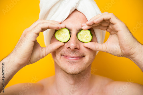 Fototapeta Funny man receiving facial mask of cucumber