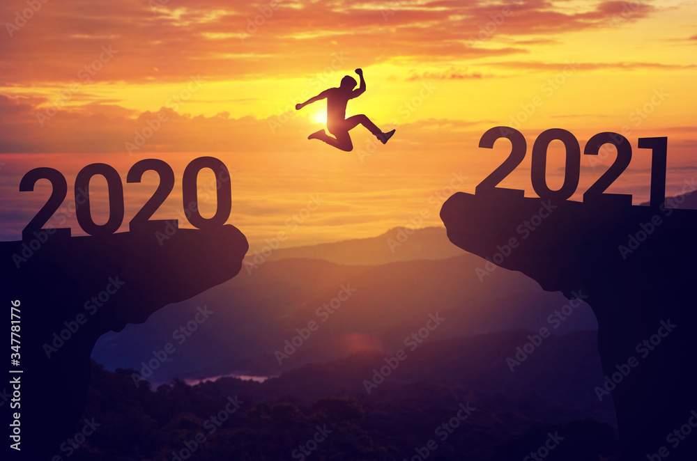 Fototapeta Silhouette man jump between 2020 and 2021 years with sunset background, Success new year concept.