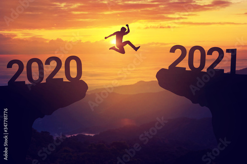 Photo Silhouette man jump between 2020 and 2021 years with sunset background, Success new year concept