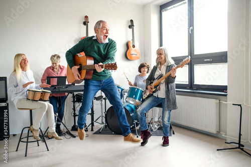 Fototapeta Group of senior people playing musical instruments indoors in band