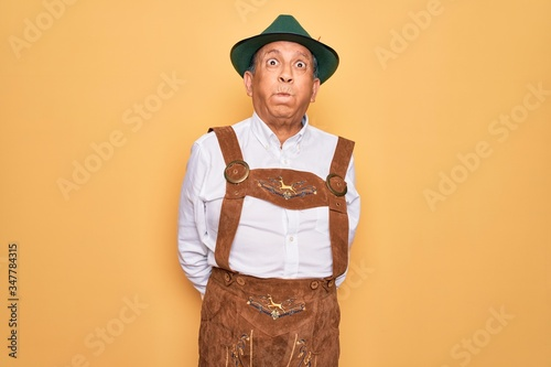 Senior grey-haired man wearing german traditional octoberfest suit over yellow background puffing cheeks with funny face Canvas-taulu