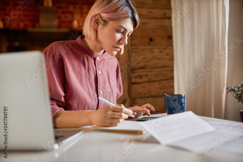 Obraz Side view of serious young female outsourced bookeeper providing accounting service for small businesses, sitting at desk with portable computer, holding pen to make notes and using calculator - fototapety do salonu