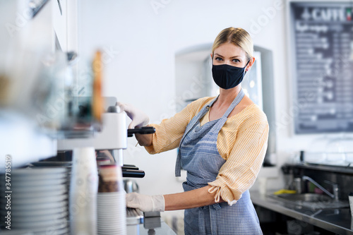Obraz Coffee shop woman owner working with face mask, open after lockdown quarantine. - fototapety do salonu