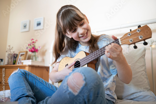 Fotografia, Obraz Girl Learning To Play Ukulele Sitting On Bed In Bedroom