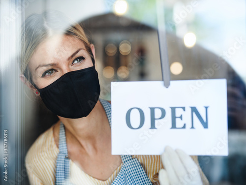 Coffee shop woman owner with face mask, open after lockdown quarantine. - 347786313