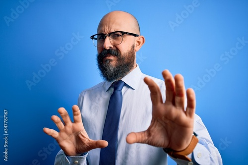 Photo Handsome business bald man with beard wearing elegant tie and glasses over blue background disgusted expression, displeased and fearful doing disgust face because aversion reaction