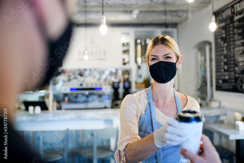 Fotomural Woman with face mask serving customer, shop open after lockdown quarantine
