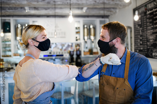 Coffee shop owners with face masks elbow bumping, open after lockdown quarantine. - 347787520