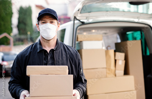 Fotografiet Delivery man courier with face mask delivering parcel boxes in town