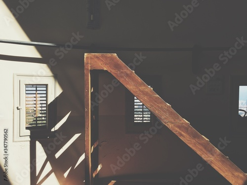 Stampa su Tela Sunlight Falling On Wooden Ladder In Building