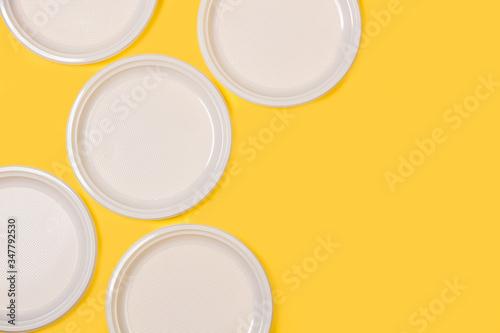 Platos redondos blanco de plástico desechable sobre fondo amarillo liso brillante y aislado Canvas Print