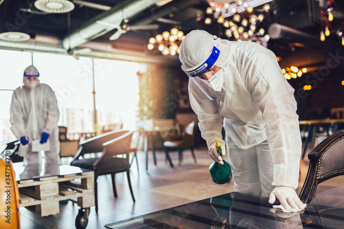 Fototapeta Professional workers in hazmat suits disinfecting indoor of cafe or restaurant, pandemic health risk, coronavirus obraz