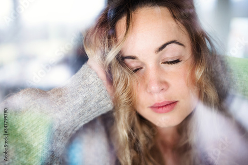 Fotografie, Obraz Young sad and depressed woman indoors by window at home.