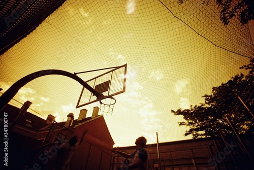Basketball Backboard And Hoop On Street In Orange Colors Of Sunset Canvas Print