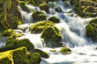 canvas print picture - Moss-covered stones and flowing river in spring