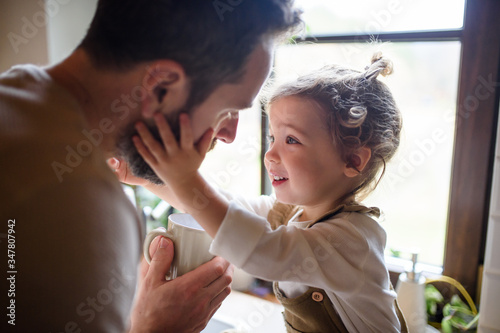 Father giving drink to sick toddler daughter indoors at home. Canvas-taulu